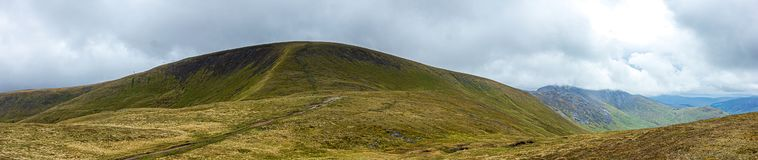 A panorama view of a Scottish mountain summit with a trail path and green heather slope under a stormy huge white clouds sky.  stock image