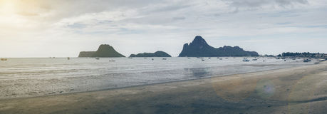 Panorama view of sea beach and traditional boat laying on the beach, mountain on background, light effect added, blue filtered. Image, flare added stock photography