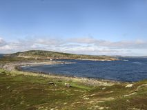 A panorama view of a sea shore with stones. An overview of the White sea coast line. A green shore and a faraway island. Blue sky with some clouds stock photo