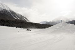A panorama view of snowy landscape and mountains and cars on the snow in the alps switzerland.  Royalty Free Stock Images