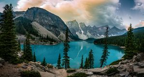 Panorama View Sunrise with turquoise waters of the Moraine lake with sin lit rocky mountains in Banff National Park of stock photo