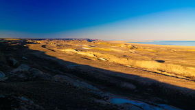 Panorama view to Aral sea from the rim of Plateau Ustyurt near Aktumsuk cape at sunset, Karakalpakstan, Uzbekistan. Panorama view to Aral sea from the rim of Stock Images