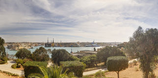 Panorama view of the Valletta city harbor area at Malta, with many historic buildings along the coastline and a red ship Royalty Free Stock Image