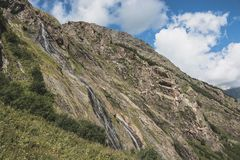 Panorama view of waterfall scene in mountains, national park of Dombay. Caucasus, Russia. Summer landscape, sunshine weather, dramatic blue sky and sunny day royalty free stock images