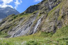 Panorama view of waterfall scene in mountains, national park of Dombay. Caucasus, Russia. Summer landscape, sunshine weather, dramatic blue sky and sunny day stock photo