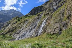 Panorama view of waterfall scene in mountains, national park of Dombay. Caucasus, Russia. Summer landscape, sunshine weather, dramatic blue sky and sunny day royalty free stock photography