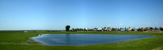 Panorama in village with blue lake and green grass Royalty Free Stock Photos