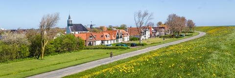 Village Oudeschild on Texel island in the Netherlands. Panorama Village Oudeschild with Martinus church, windmill and trraditional gable houses on the Wadden stock images