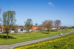 Village Oudeschild on Texel island in the Netherlands. Panorama Village Oudeschild withwindmill and trraditional gable houses on the Wadden island Texel in the royalty free stock photography