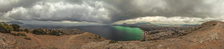 Panorama, vista horizontal de montanhas crimeanas com litoral rochoso, o Mar Negro antes da chuva Fotos de Stock Royalty Free