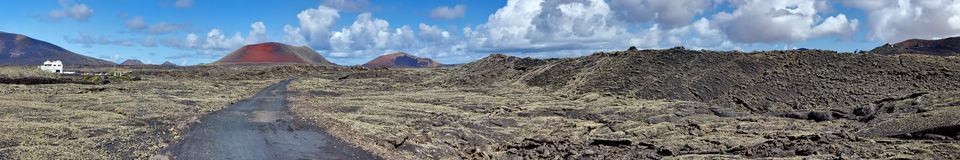 Panorama of volcanic field. Lanzarote, Canary Islands. Panorama of a volcanic field with Caldera Colorada volcano in background. Canary Islands, Lanzarote Stock Images