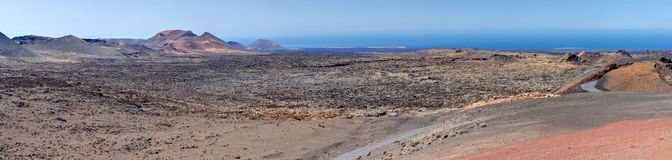 Panorama from volcanic hill on Lanzarote. Canary Islands. Timanfaya National Park. Ocean in background Stock Photos