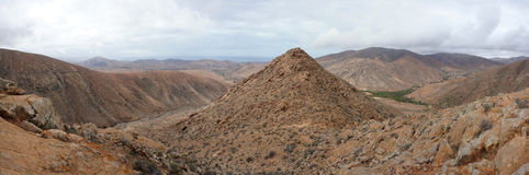 Panorama of volcanic hills, Fuerteventura. Canary Islands. Ocean in background Royalty Free Stock Photography