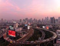Panorama von Bangkok an der Dämmerung mit Wolkenkratzern im Hintergrund u. im starken Verkehr auf erhöhten Schnellstraßen u. Krei stockbild