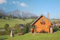 Panorama von Bergen Belianske Tatry und von kleinen Blockhaus in Zdiar-Dorf Stockbild