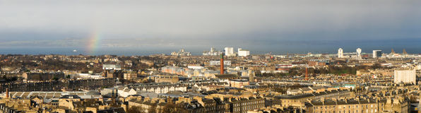 Panorama von Edinburgh mit einem kleinen Regenbogen, im Hintergrund das Wasser der Förde von weiter und hinter ihr das gegenüberl Stockbilder