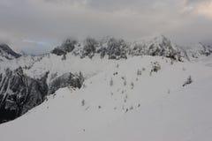 Panorama von französischen Alpen mit den Gebirgszügen umfasst im Schnee und in den Wolken im Winter Lizenzfreie Stockbilder
