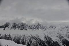 Panorama von französischen Alpen mit den Gebirgszügen umfasst im Schnee und in den Wolken im Winter Lizenzfreies Stockfoto