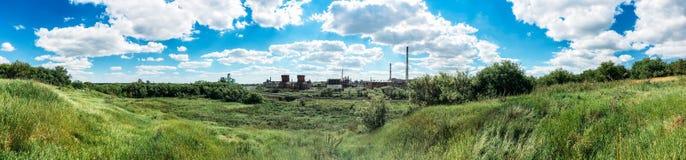 Panorama von grünen Hügeln und von Industrieanlage mit Kaminen Stockbild