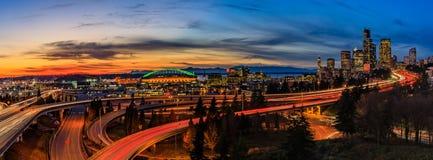 Panorama von im Stadtzentrum gelegenen Skylinen Seattles über dem I-5 I-90 Autobahnaustausch bei Sonnenuntergang mit langen Belic stockfotos