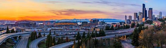 Panorama von im Stadtzentrum gelegenen Skylinen Seattles über dem I-5 I-90 Autobahnaustausch bei Sonnenuntergang mit langen Belic lizenzfreie stockbilder