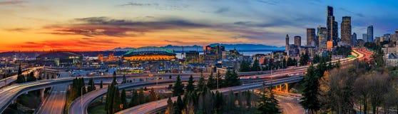 Panorama von im Stadtzentrum gelegenen Skylinen Seattles über dem I-5 I-90 Autobahnaustausch bei Sonnenuntergang mit langen Belic lizenzfreies stockfoto