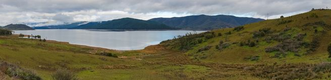 Panorama von malerischem See und von Wald bedeckte Berge lizenzfreies stockbild