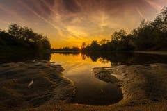 Panorama von wildem Fluss mit Reflexion des bewölkten Himmels des Sonnenuntergangs, im Herbst Stockbild