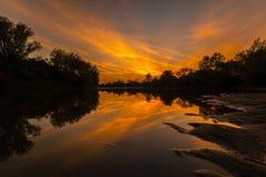 Panorama von wildem Fluss mit Reflexion des bewölkten Himmels des Sonnenuntergangs, im Herbst Stockbilder
