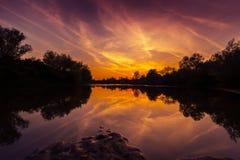 Panorama von wildem Fluss mit Reflexion des bewölkten Himmels des Sonnenuntergangs, im Herbst Lizenzfreies Stockfoto