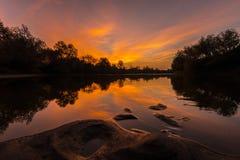 Panorama von wildem Fluss mit Reflexion des bewölkten Himmels des Sonnenuntergangs, im Herbst Stockfotografie
