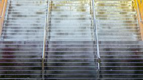 Panorama Wide flight of stairs with shiny metal handrails underneath a building. The stairway leads to the sunny outdoors from the passageway stock photos