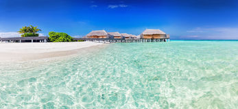 Panorama of wide sandy beach with water villas on a tropical isl Royalty Free Stock Photo