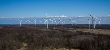 Panorama with wind generators in the spring dark forest Royalty Free Stock Image