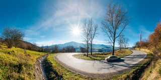 Panorama of winding serpentine road in november. Panorama of winding serpentine road. lovely autumn afternoon with bright sun on a blue sky. leafless trees by royalty free stock photos