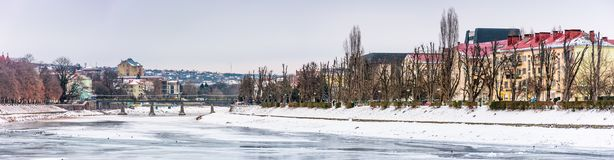 Panorama of winter cityscape on the river Uzh. Lovely travel background with Kyiv embankment, pedestrian bridge and some architecture of central part of old Royalty Free Stock Photography