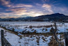 Panorama of a winter landscape at sunset in the mountains. Dusk or dawn panorama of a winter landscape in the mountains with cattle in the fields and snow on the royalty free stock photos