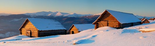 Panorama of winter mountains. Wooden small houses in mountains. Mountains Carpathians, Ukraine. The picture is made at a dawn in January royalty free stock images