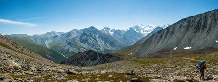 Panorama, a woman climbs the pass Karaturek. Trekking in the Altai Mountains Royalty Free Stock Photos