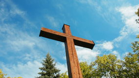 Panorama of Wooden Cross among Trees on the background of Sky and Moving Clouds. Horizontal Panorama of Big Wooden Cross is Standing among the Trees on the stock footage