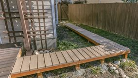 Panorama Wooden walkway inside the yard of a home viewed on a sunny day. The walkway is connected to a wooden deck with a reflective glass door leading inside stock photos