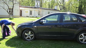 Panorama of young man clean wash black favorite car with foam stock video footage