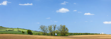 Panorama z niebieskim niebem i gajem z małą kaplicą Obraz Stock