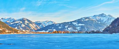 Panorama of Zeller see lake in evening blue shadows, Zell am See, Austria. Walk along the Esplanade embankment of frozen Zeller see lake with a view on its stock image