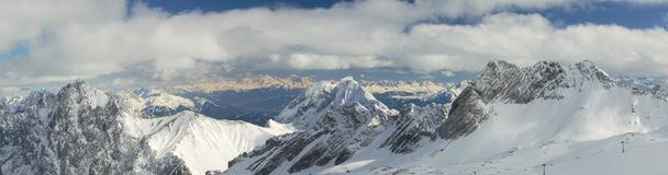 Dramatic Panorama of  Snow Capped Mountain Peaks i. Wide panoramic view of the German and Austrian Alps from the Zugspitze Glacier, the highest mountain in Stock Photos