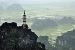 Panoramaansicht von Reisfeldern, von Felsen und von Bergspitzenpagode von Stockfotos