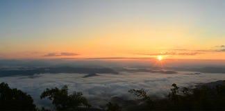 Panoramabergsikt på solresningen med mist i fältet Arkivbild