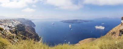 Panoramabild der felsigen Küstenlinie von Santorini, von Griechenland mit dem Kapital Fira und von einigen Kreuzschiffen stockfotografie