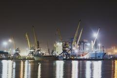 Panoramabild des belichteten Frachthafens in Novorossiysk, Russland nachts mit Containerbahnhöfen, Frachtschiff und Kränen und Stockfotos