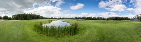 Panoramabilden av golfklubben med dammet och gör perfekt grönt gräs arkivfoton